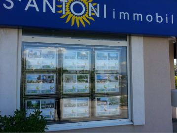 La vitrine de l'agence s'antoni immobilier de sète éclairée S'antoni immobilier